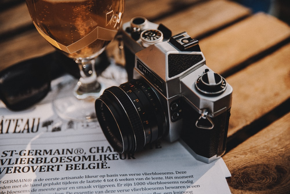 black and silver dslr camera beside clear wine glass