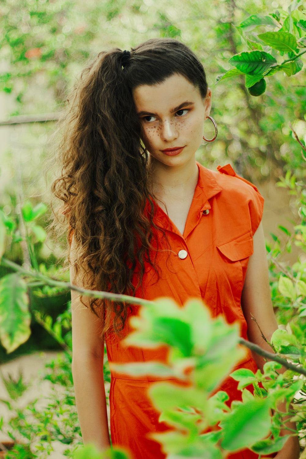 woman in red button up sleeveless shirt holding red rose