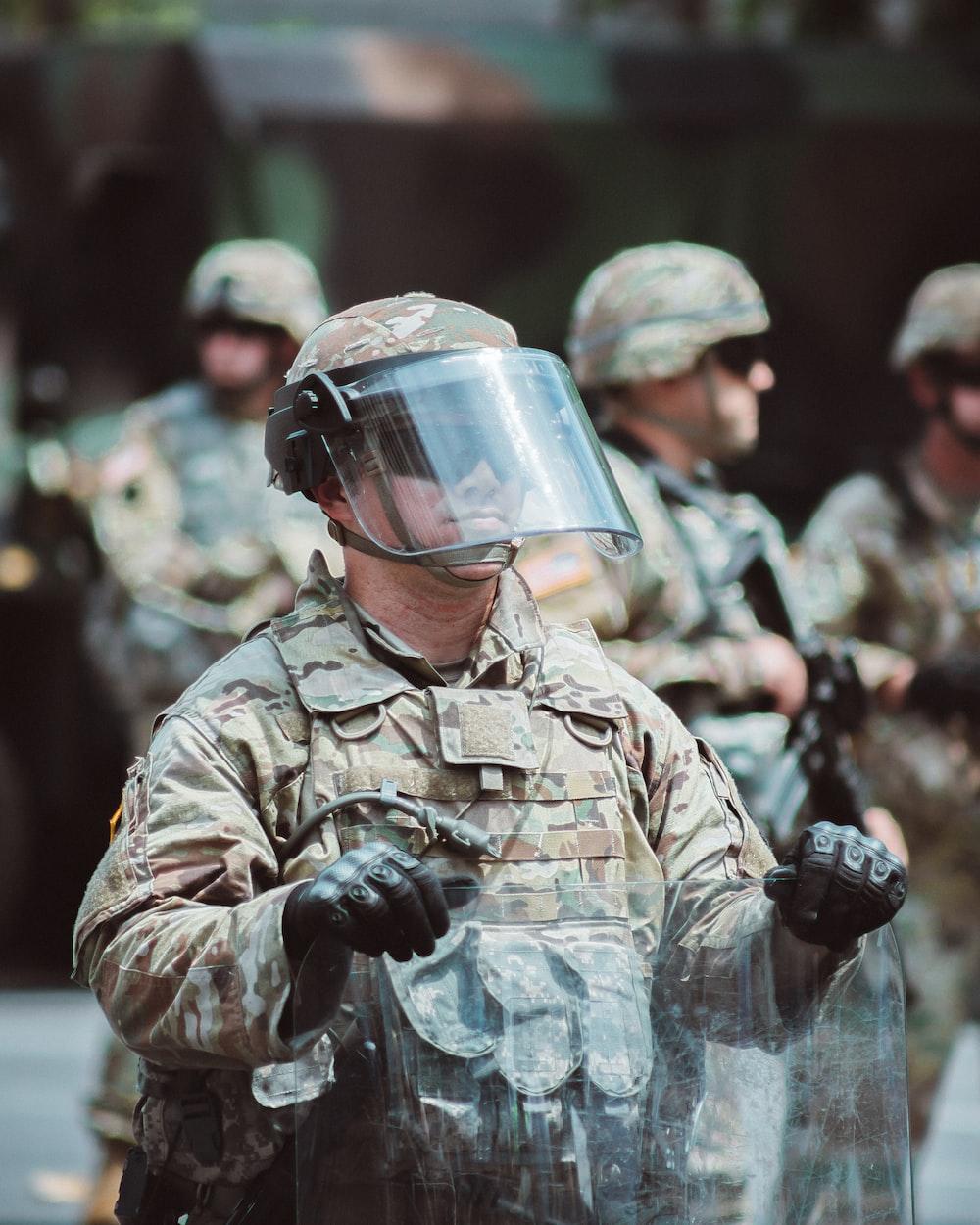 man in brown and black camouflage uniform wearing helmet