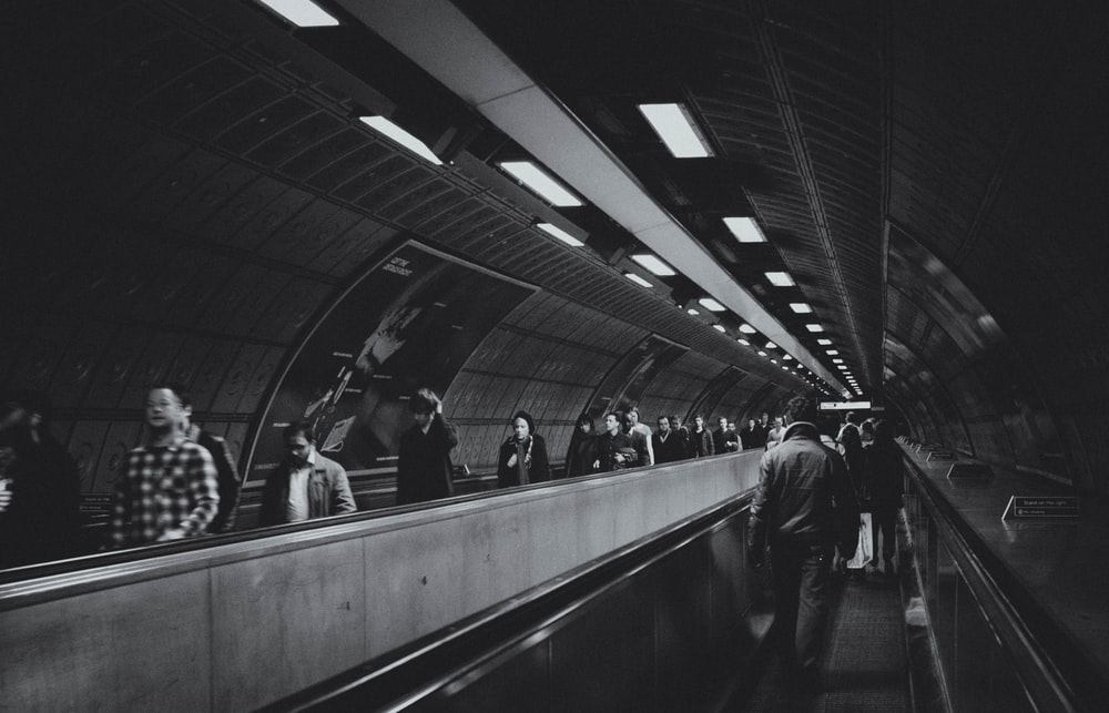 people walking on the train station in grayscale photography