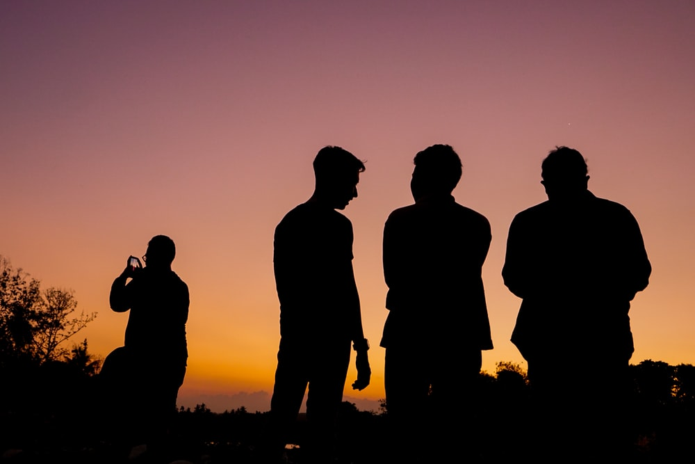 silhouette of 3 men standing on grass field during sunset