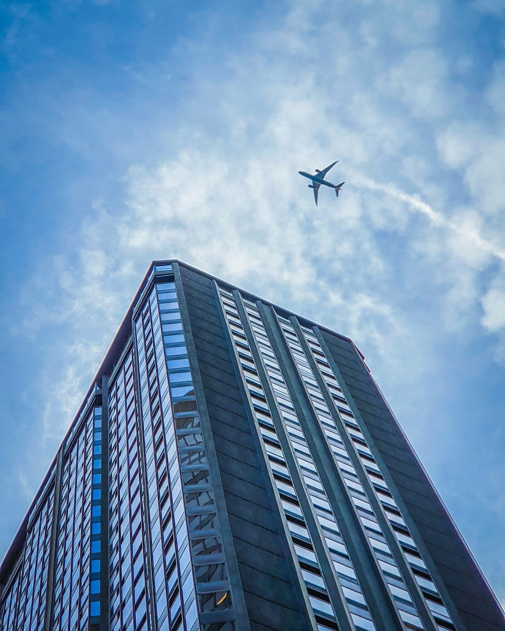 white airplane flying over gray concrete building during daytime