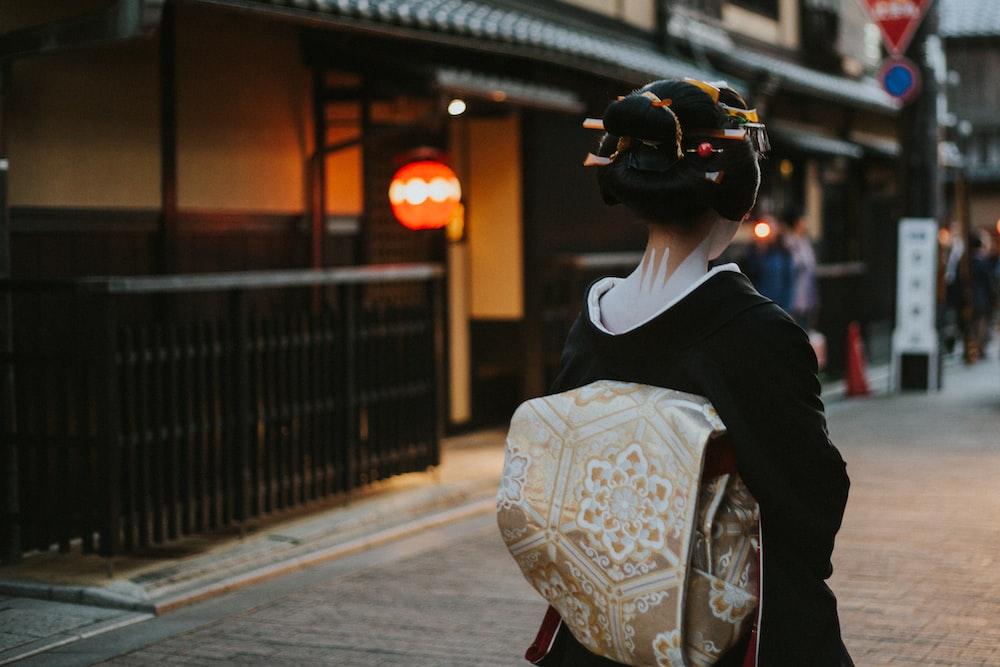woman in black and white floral kimono walking on sidewalk during daytime