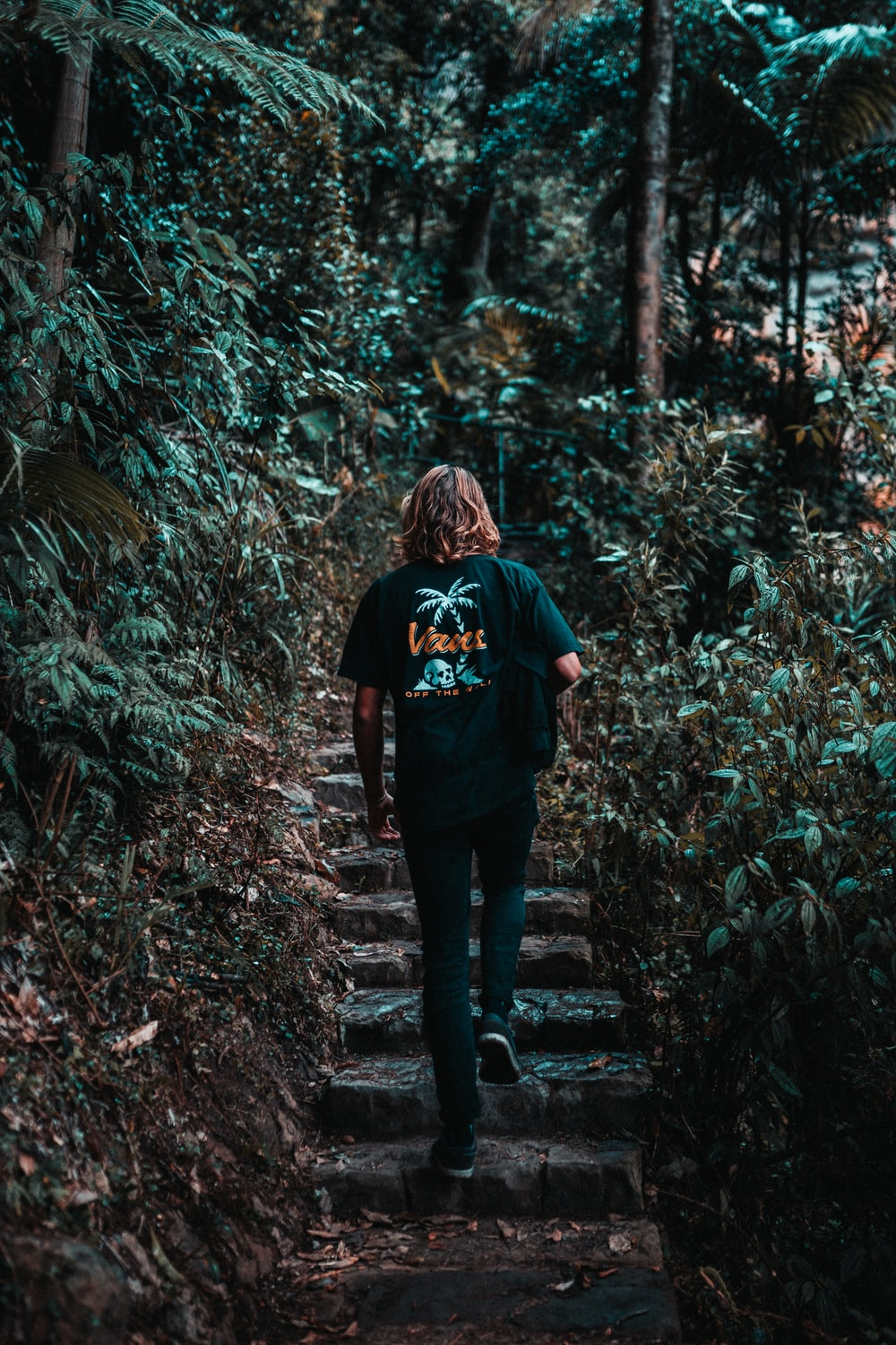 woman in black jacket standing on forest during daytime