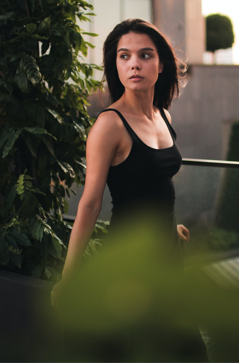 woman in black tank top standing beside green plant