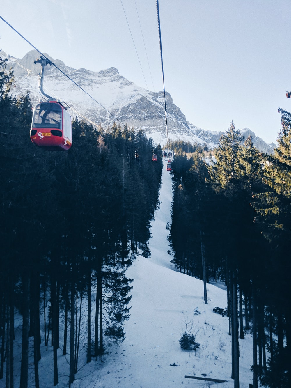red cable car over snow covered mountain during daytime