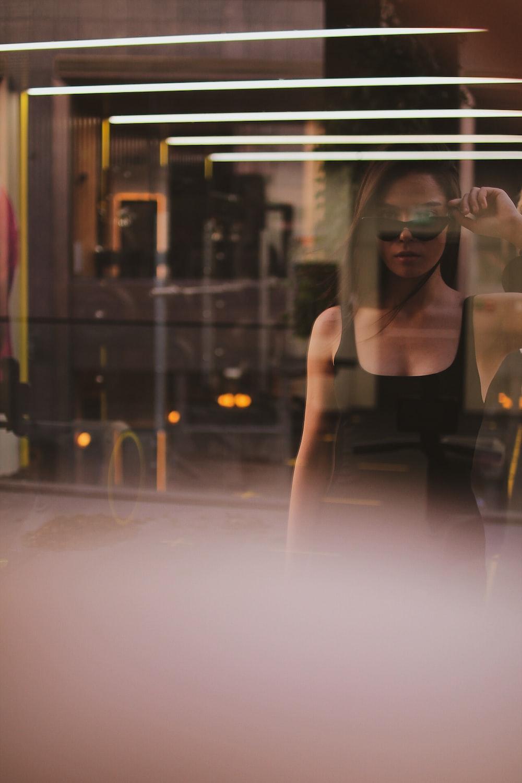 woman in black tank top standing near glass window
