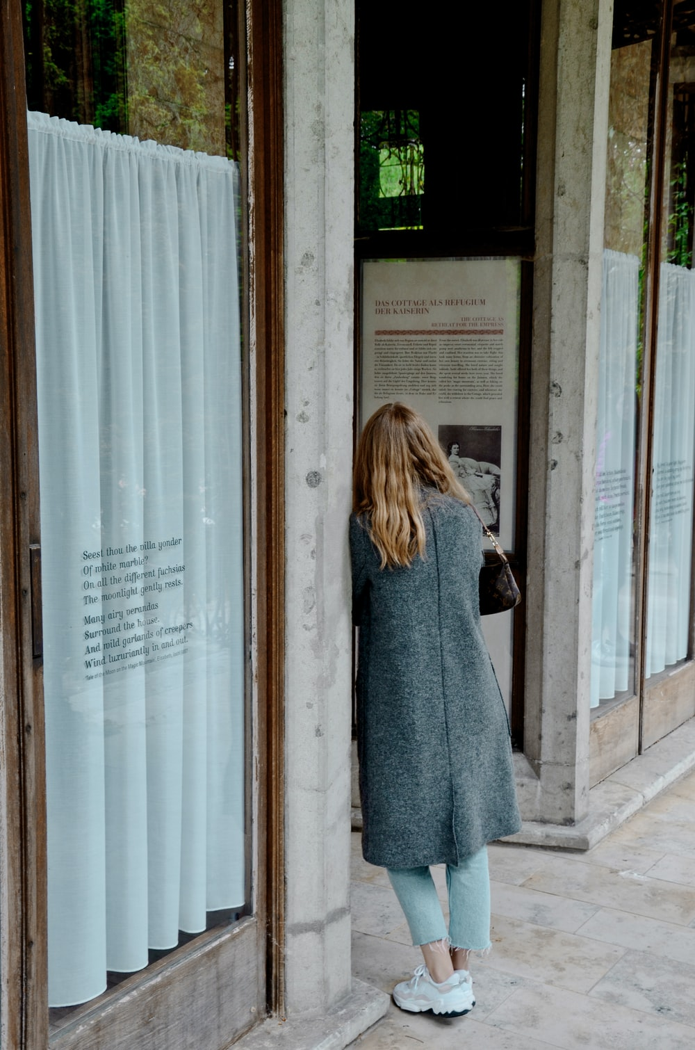 woman in gray coat standing in front of glass window