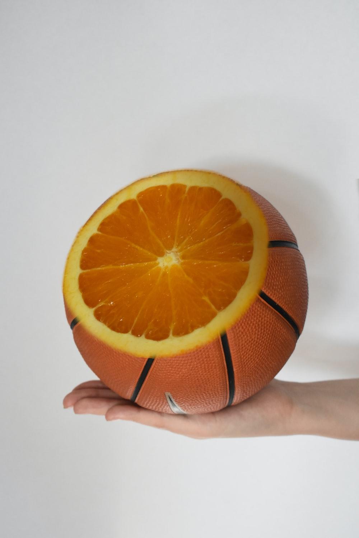 person holding orange fruit on white surface