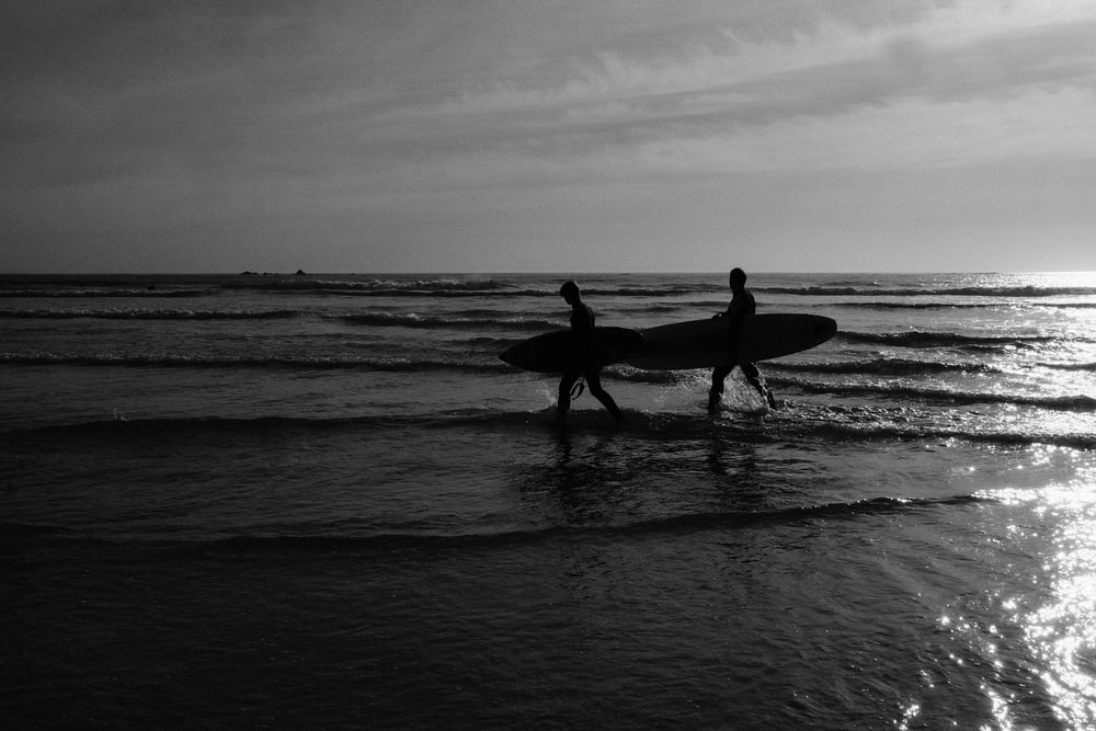 grayscale photo of 2 men and woman holding surfboard on beach