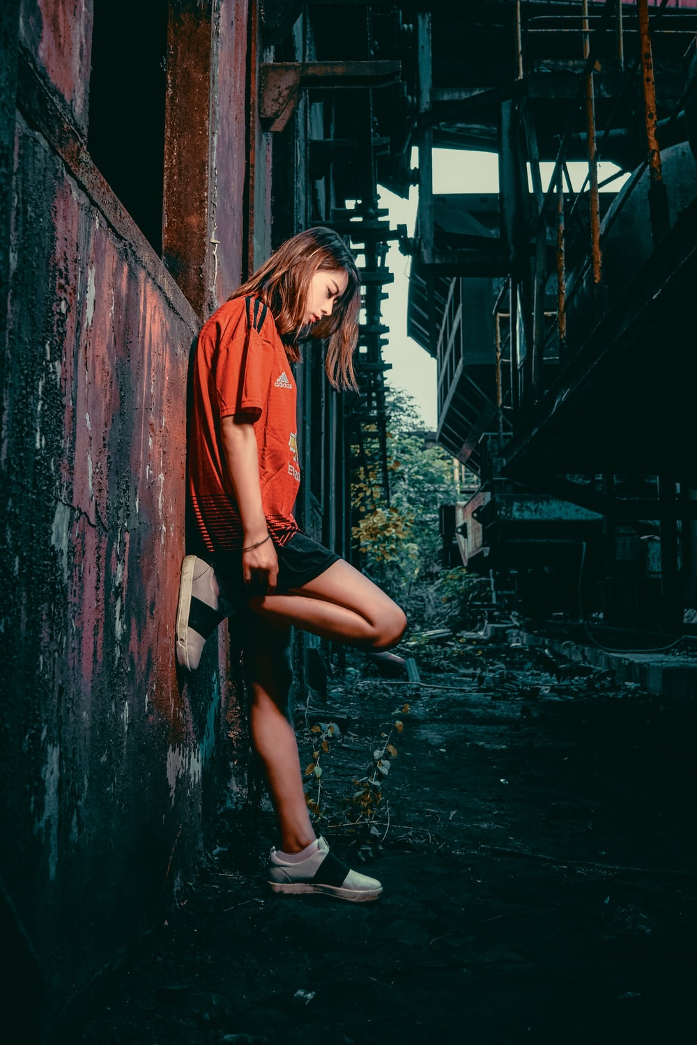 woman in orange jacket and black shorts sitting on brown wooden fence