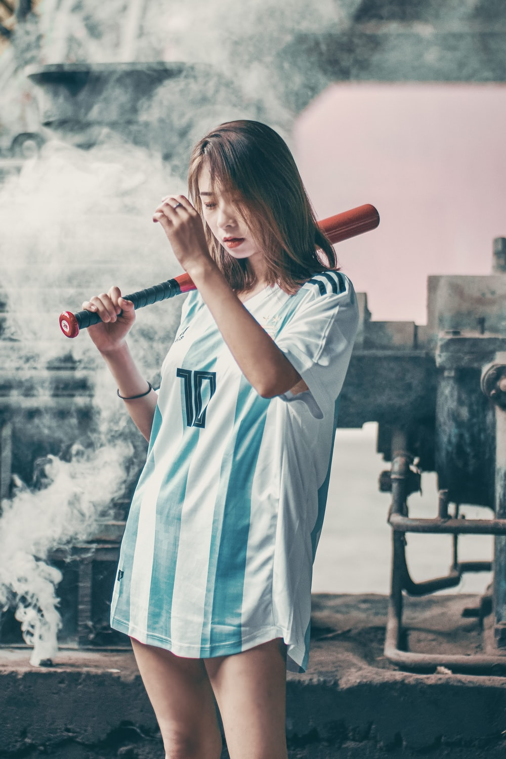 woman in white and blue long sleeve shirt holding red baseball bat