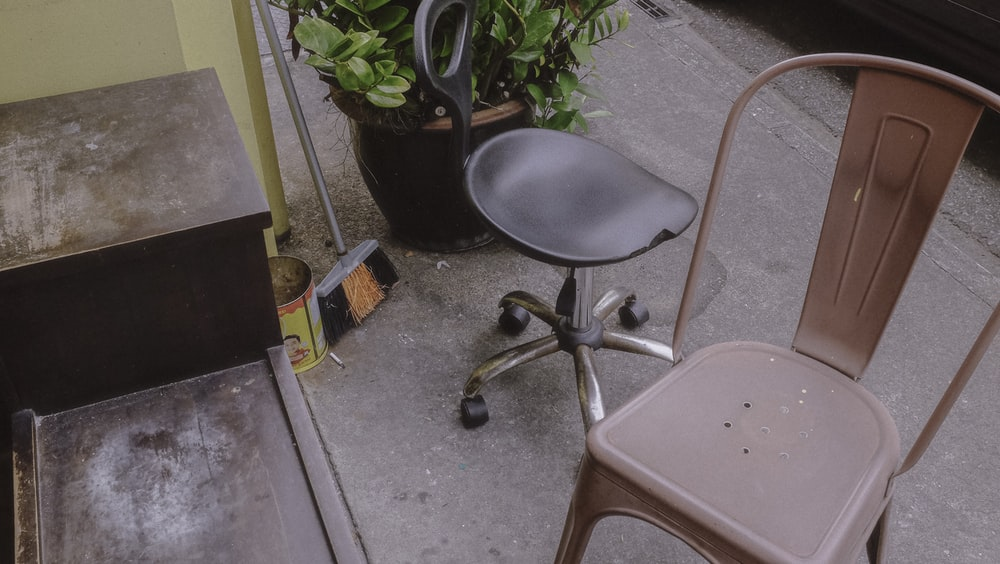 black and gray rolling chair beside green plant