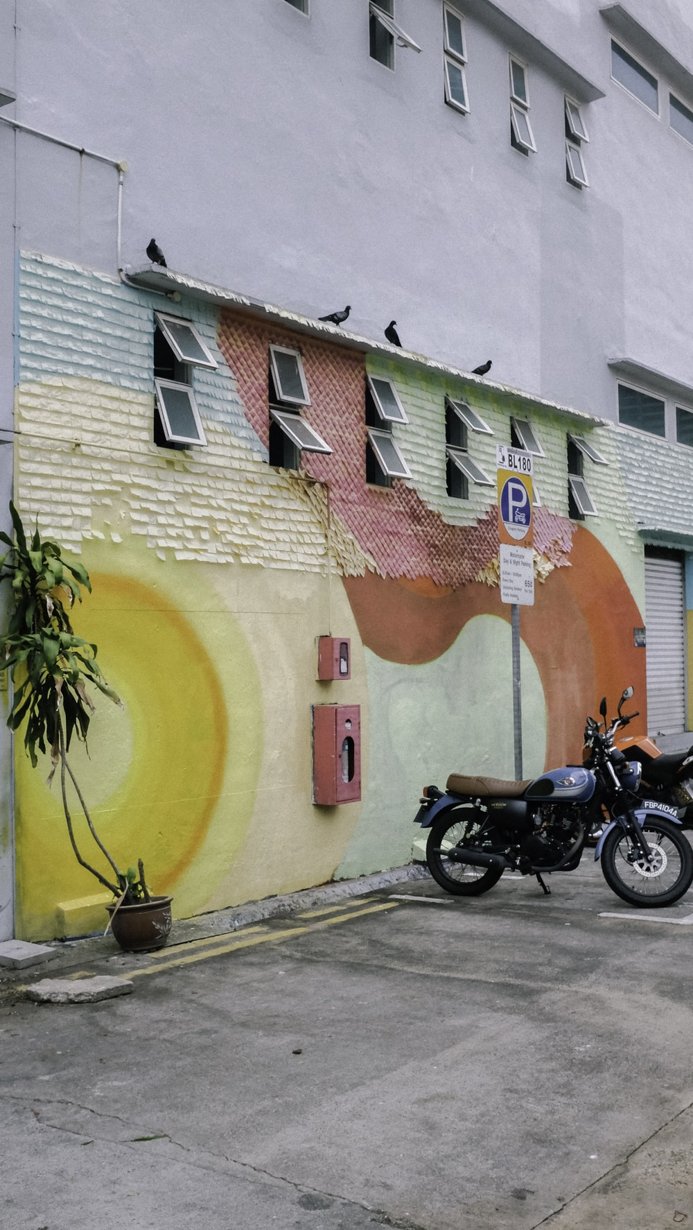 black motorcycle parked beside red yellow and blue concrete building during daytime