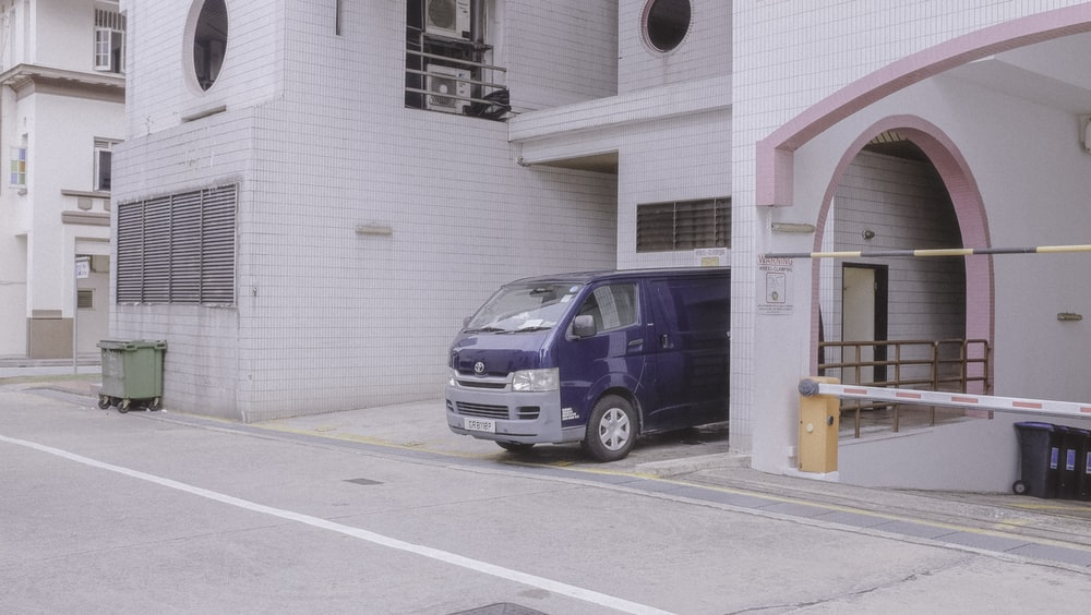white and blue van parked beside white building