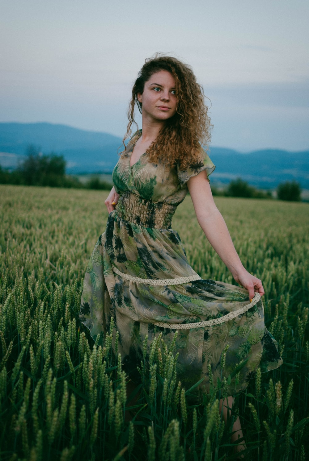 woman in green and brown floral dress standing on green grass field during daytime