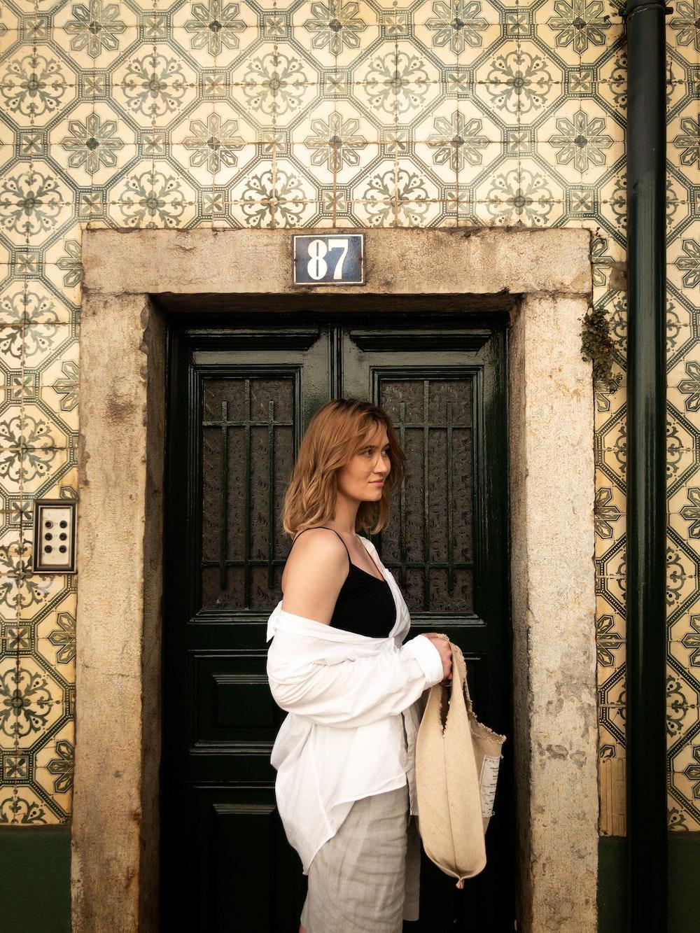 woman in white dress standing in front of black wooden door