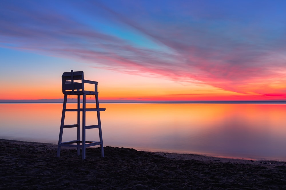 brown wooden chair on brown sand near body of water during sunset