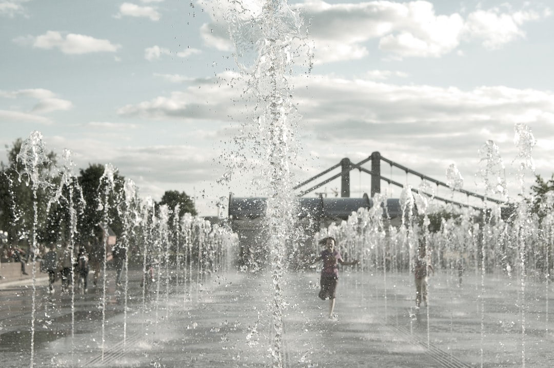 A girl running between water fountain in Moscow