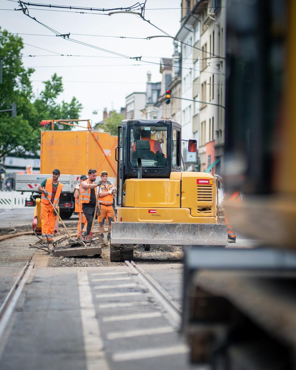 man in orange jacket standing beside yellow truck during daytime