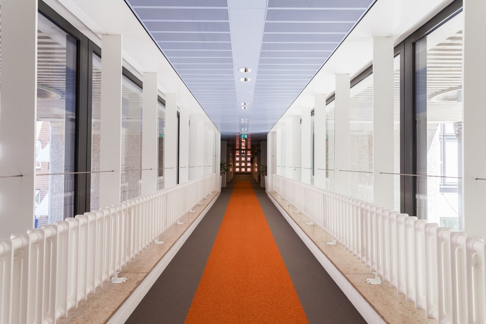 white and brown hallway with white metal railings