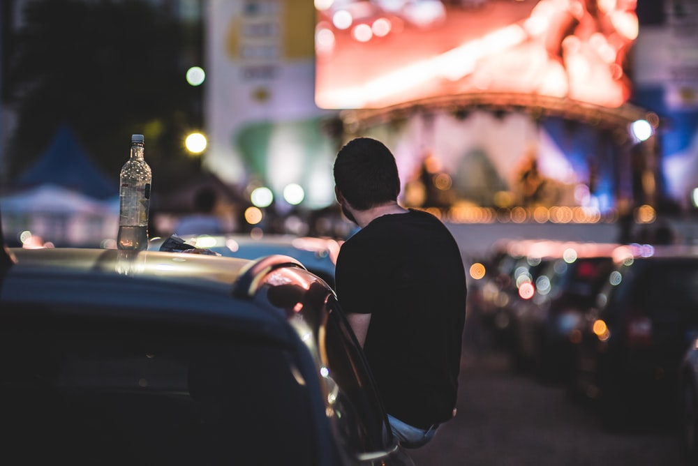 man in black suit standing near road during night time