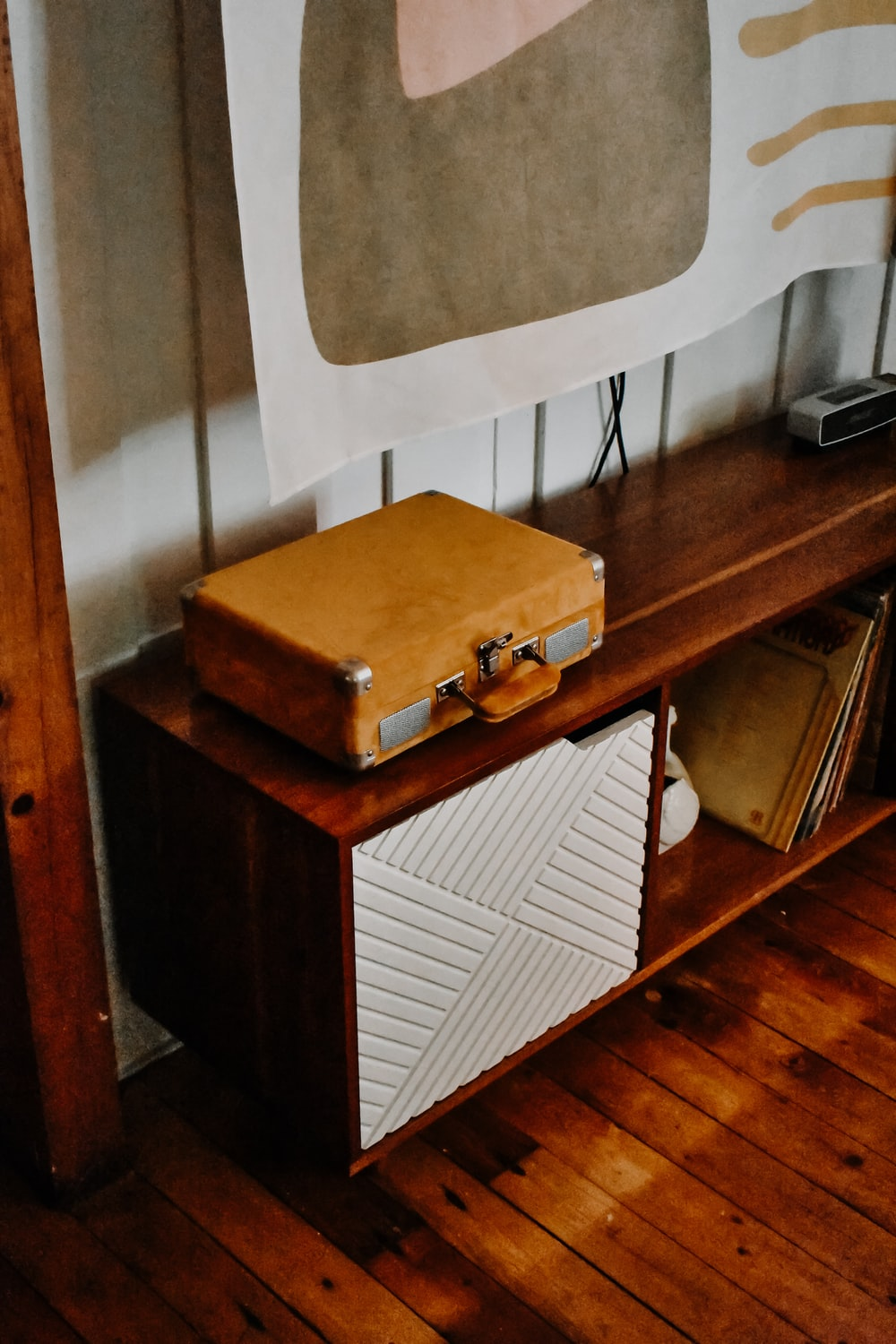 brown wooden drawer chest beside white wall