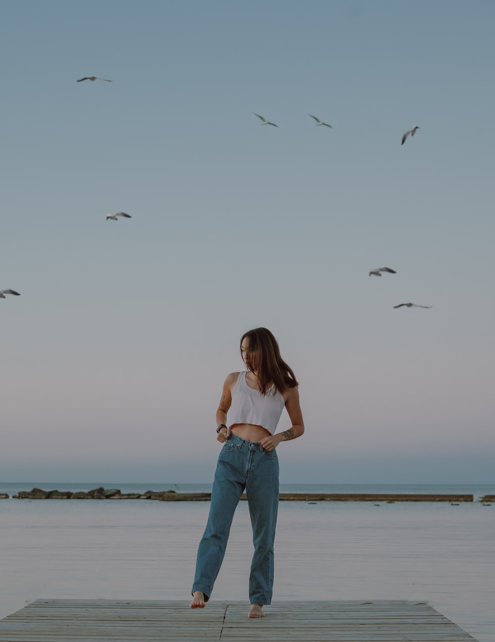 woman in blue denim jeans standing on seashore during daytime