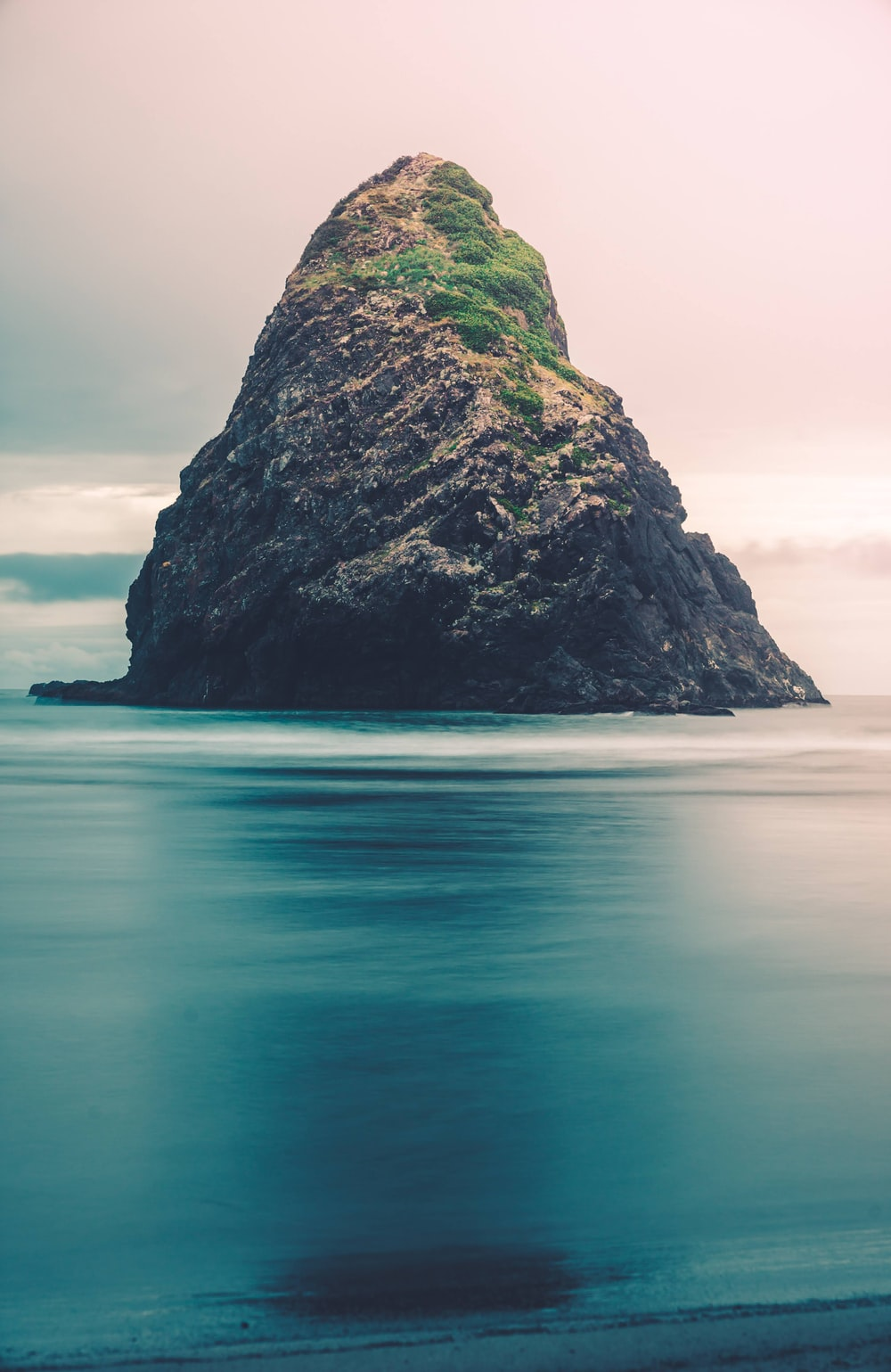 green and black rock formation on blue sea under white sky during daytime