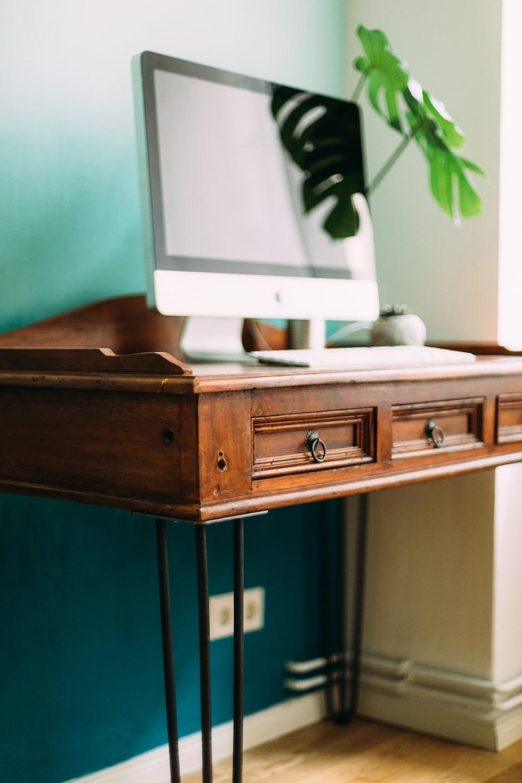 silver imac on brown wooden desk