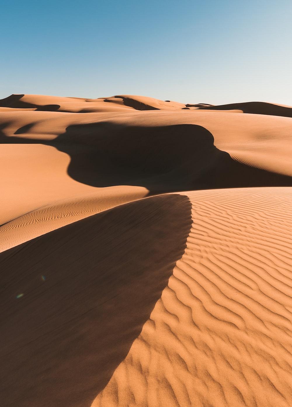 brown sand dunes under blue sky during daytime