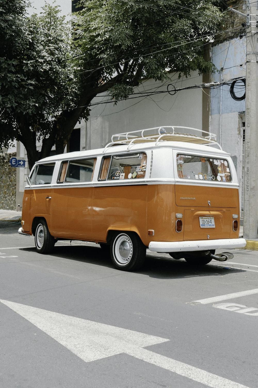 orange and white volkswagen t-2 parked on sidewalk during daytime