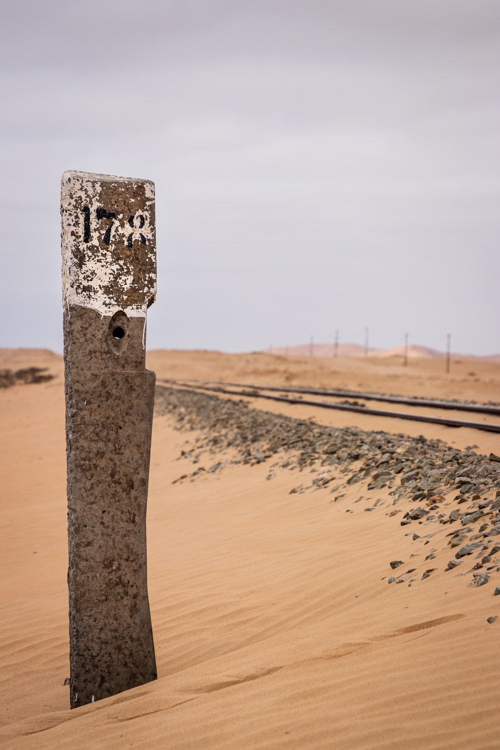 brown wooden post on brown sand during daytime
