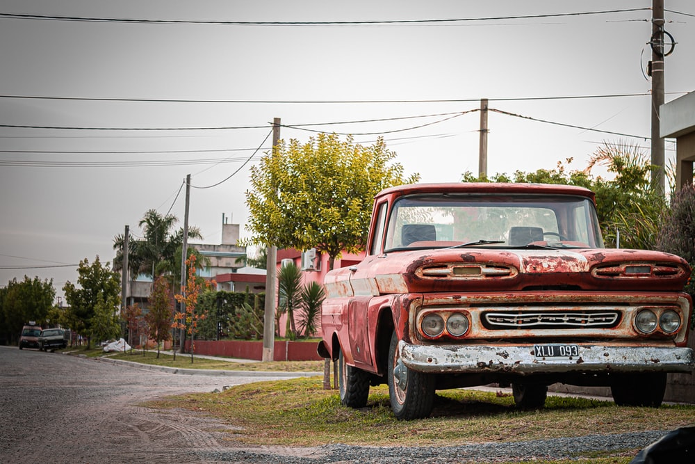 red chevrolet single cab pickup truck parked on the side of the road during daytime