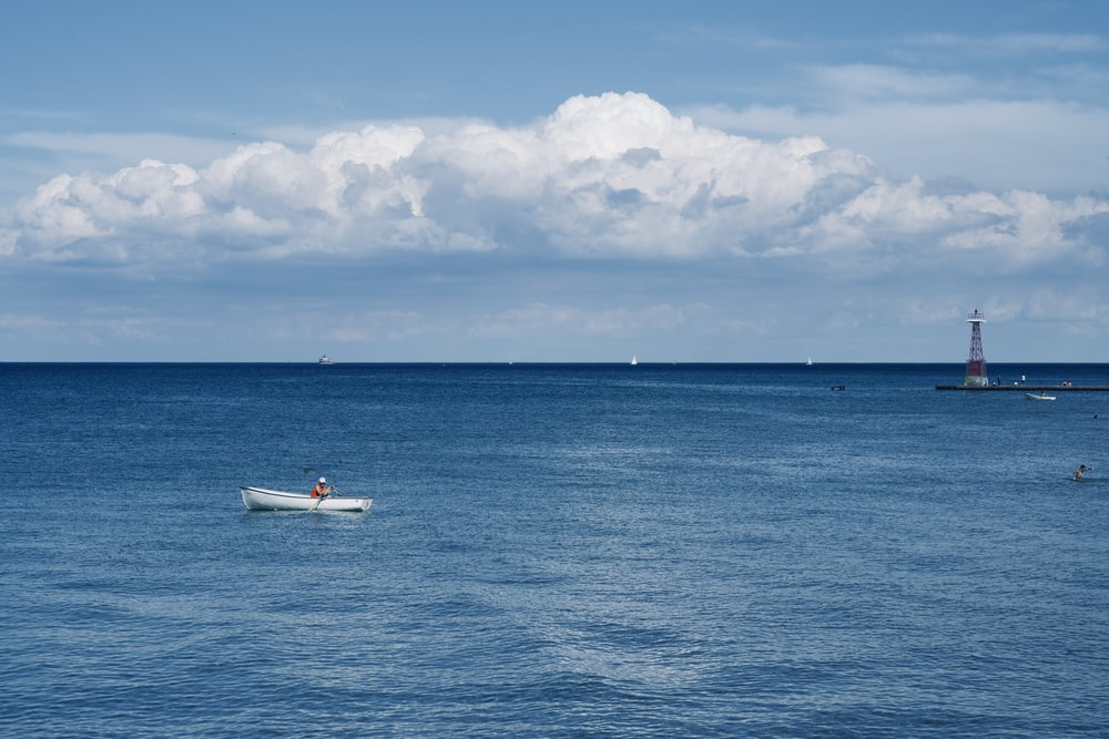 white boat on sea under blue sky and white clouds during daytime