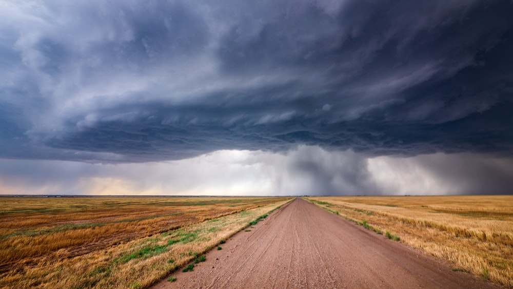 brown dirt road under gray clouds