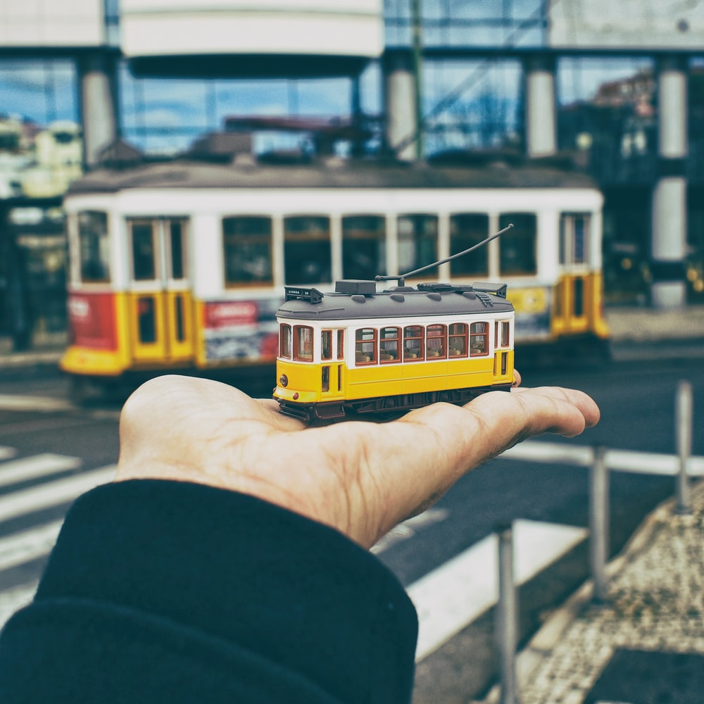 person holding yellow and white train toy