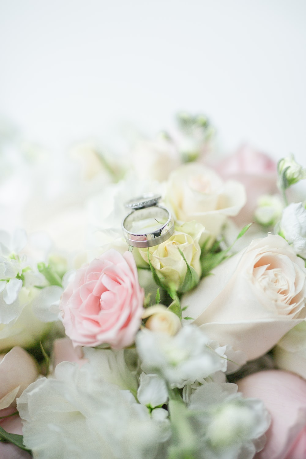 silver ring on white and pink roses bouquet