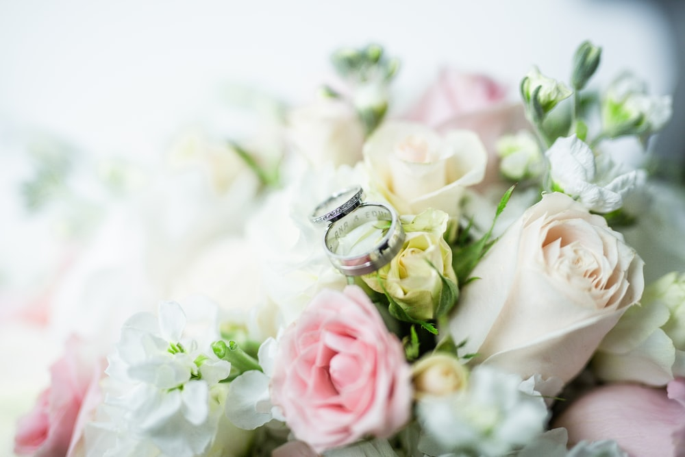 silver diamond ring on white and pink roses bouquet