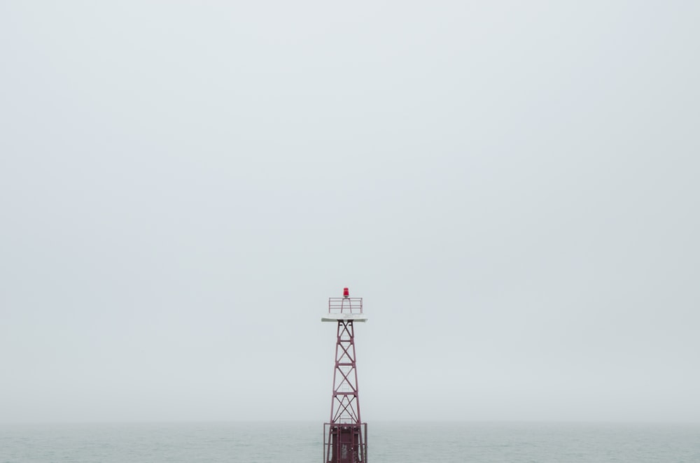 red and white tower on the sea