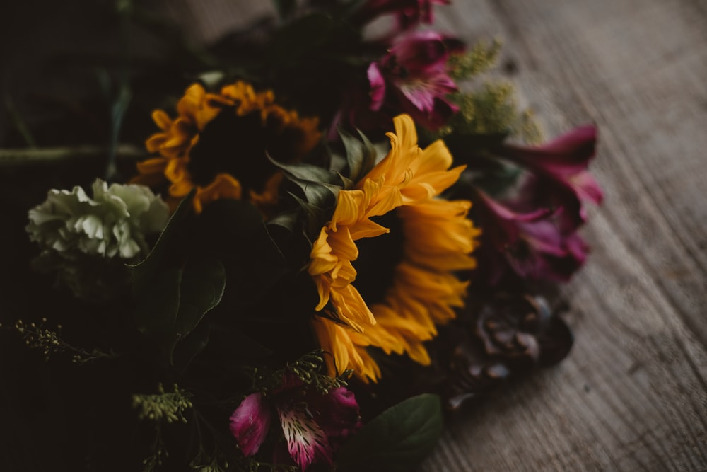 yellow and red flower on gray wooden table