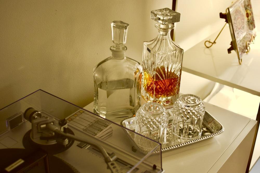 clear glass bottles on white metal rack