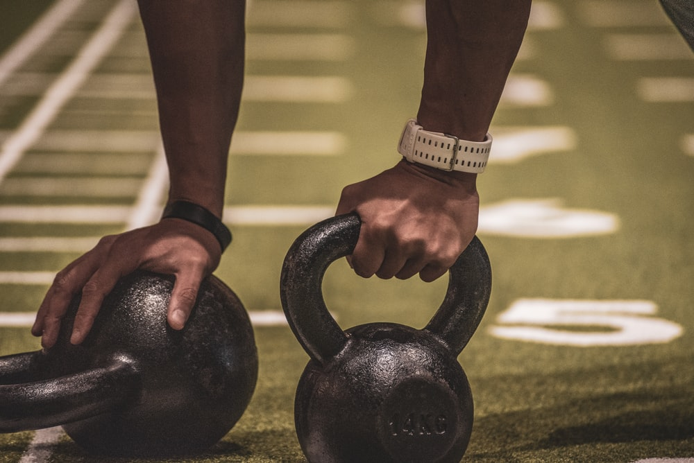 person holding black kettle bell