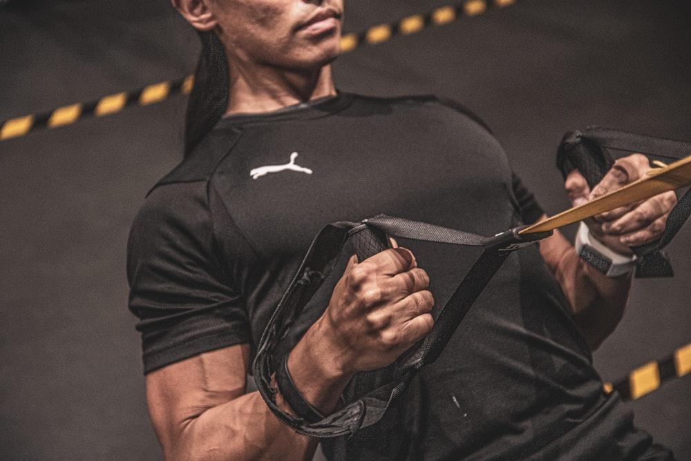 man in black nike crew neck t-shirt holding black sunglasses