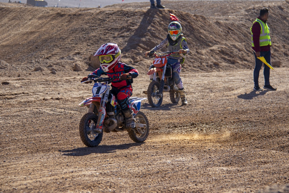 2 men riding motocross dirt bikes on brown field during daytime
