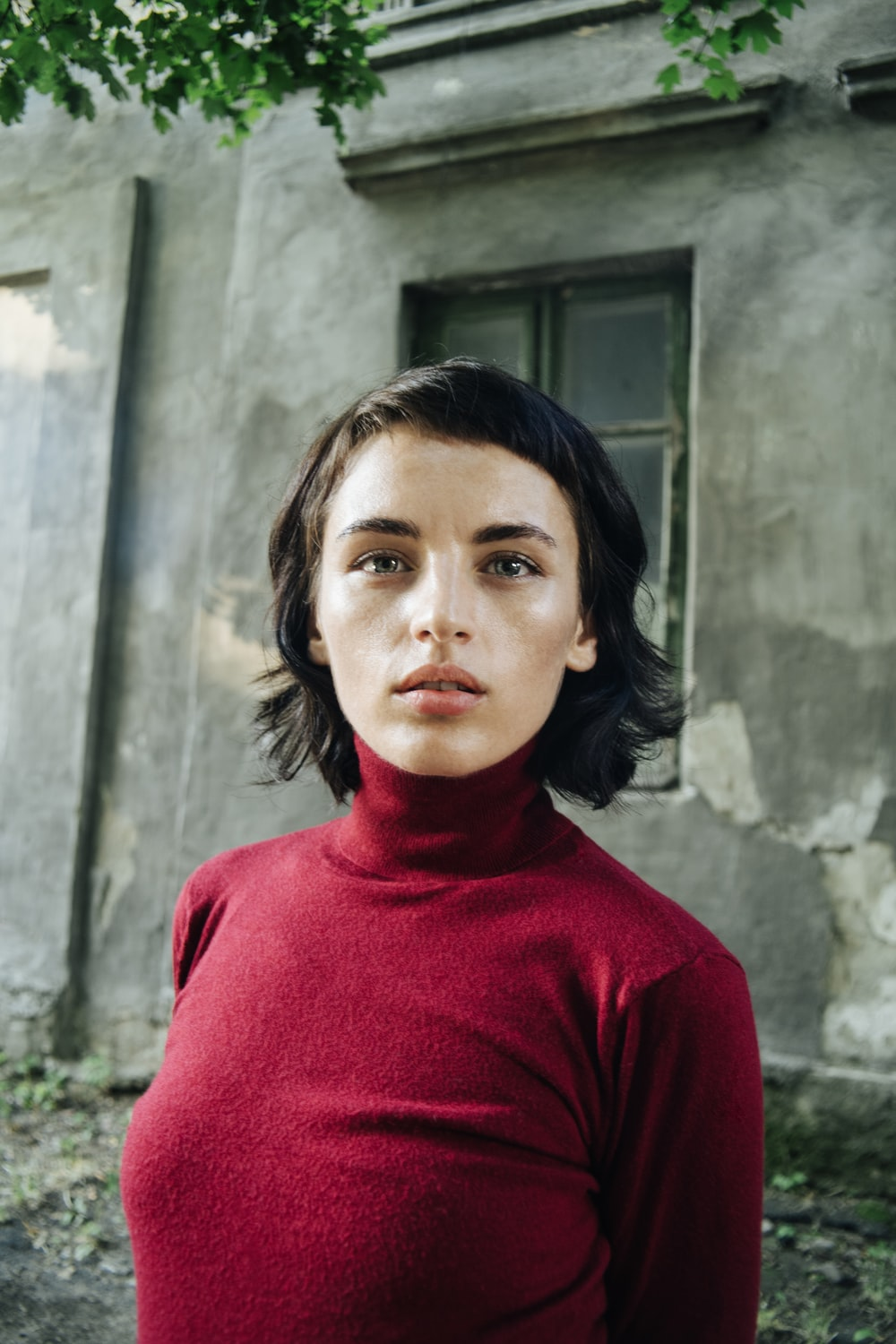 woman in red turtleneck sweater standing beside gray concrete wall