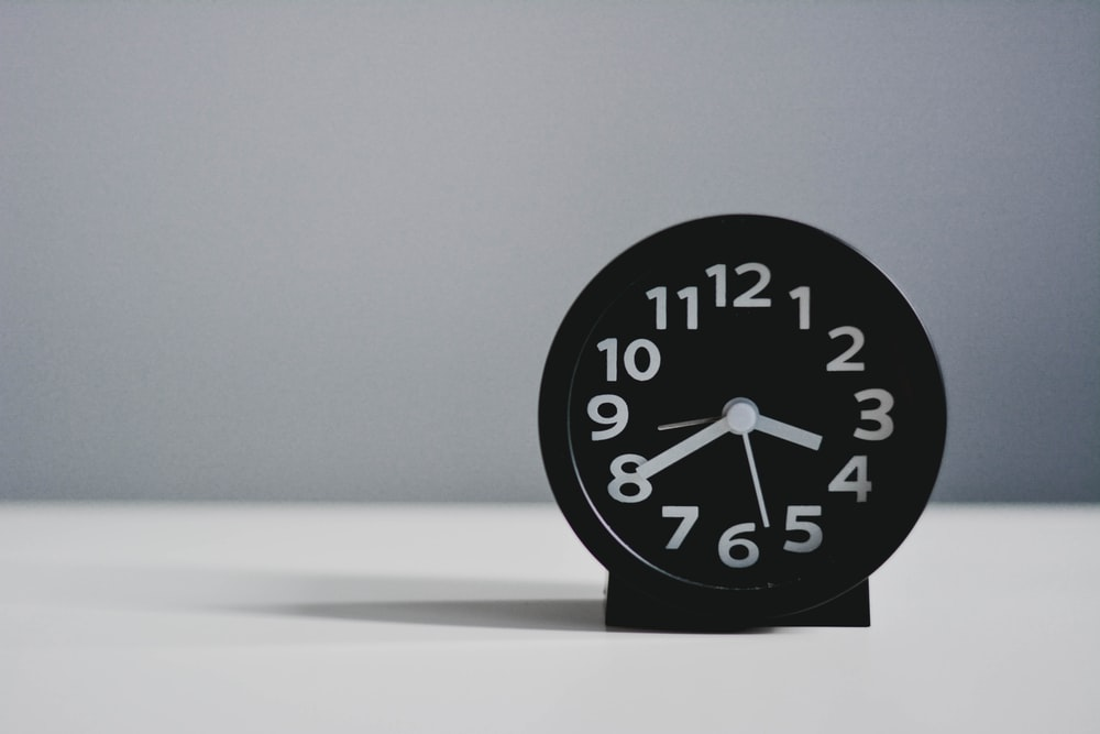black round analog clock at 10 00