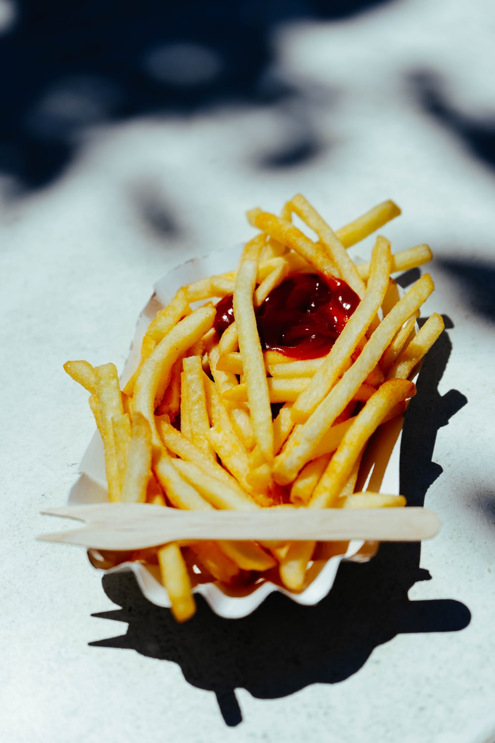 french fries with ketchup on white paper