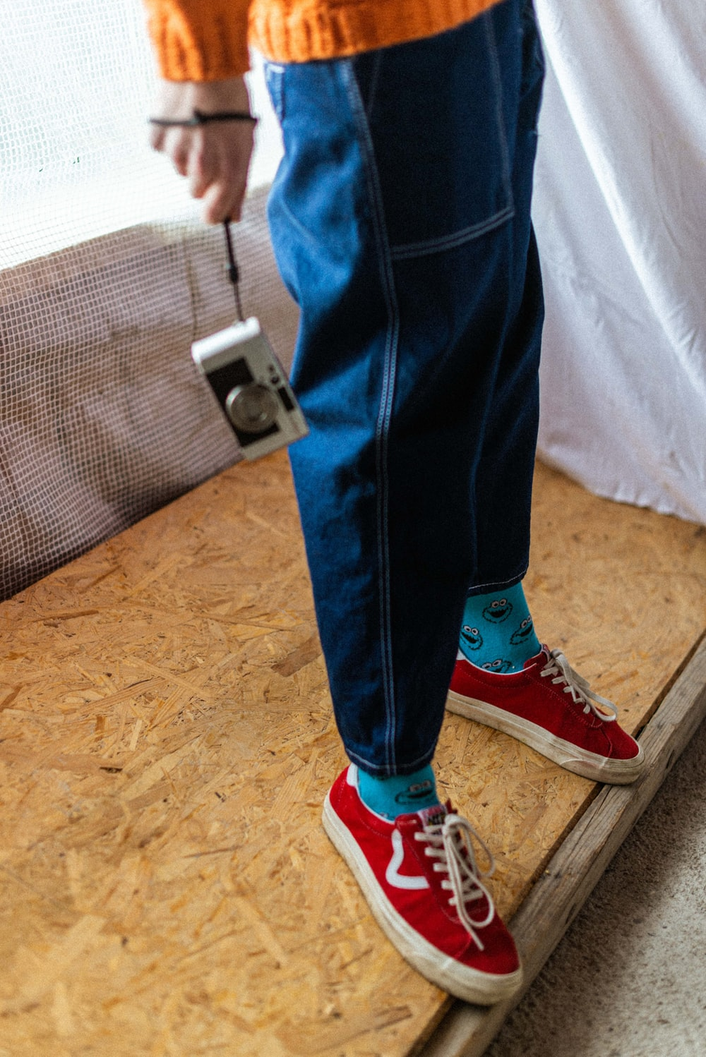 person in blue denim jeans and red converse all star high top sneakers