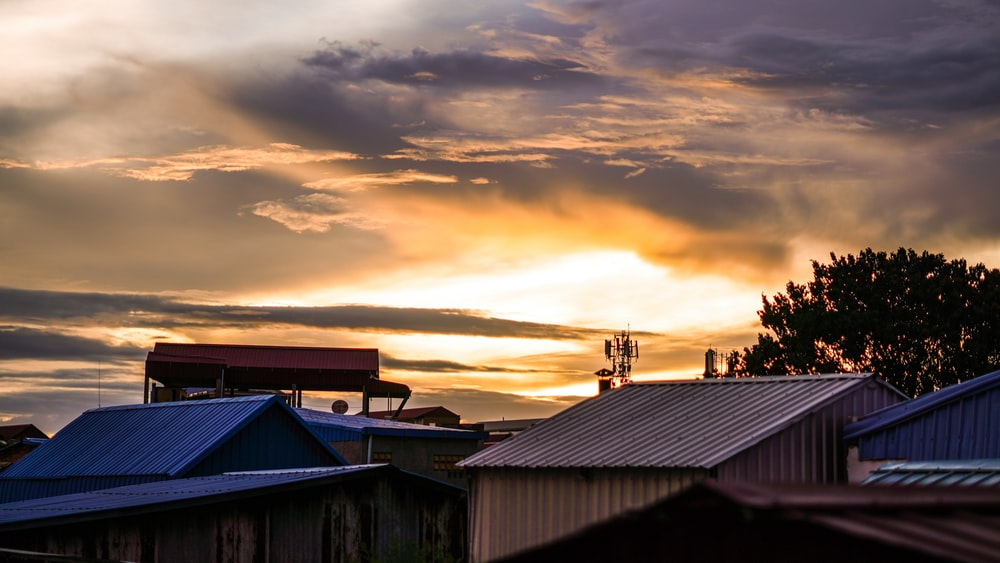 houses under cloudy sky during sunset